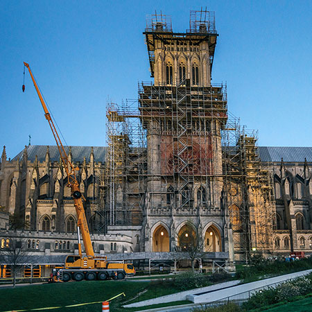 Against a dusky dark blue sky, the National Cathedral stands blocked by extensive scaffolding and a tall yellow crane.