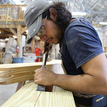 A young man fine tunes a cut in a piece of lumber using a hand tool that looks like a wide chisel.
