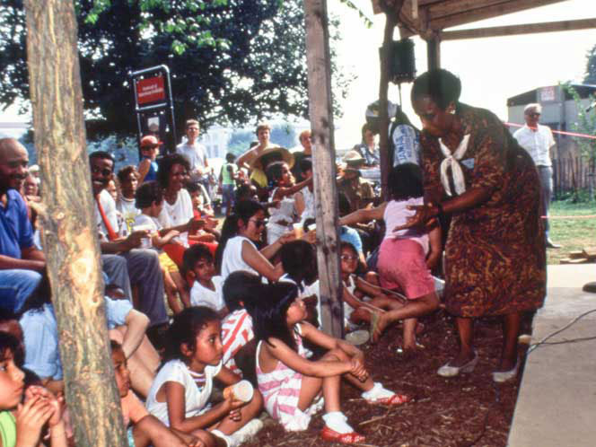 Olive Lewin engages a group of young audience members from one of the stages at the 1989 Folklife Festival. <i>Ralph Rinzler Folklife Archives and Collections, Smithsonian Institution</i>