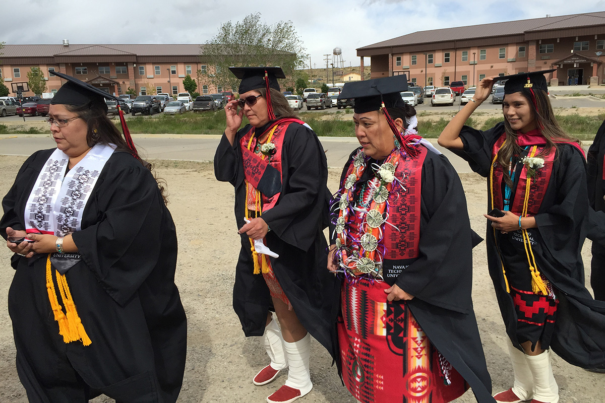 Four women in black graduation caps and gowns, plus sashes with Native geometric designs, walk across a parking lot.