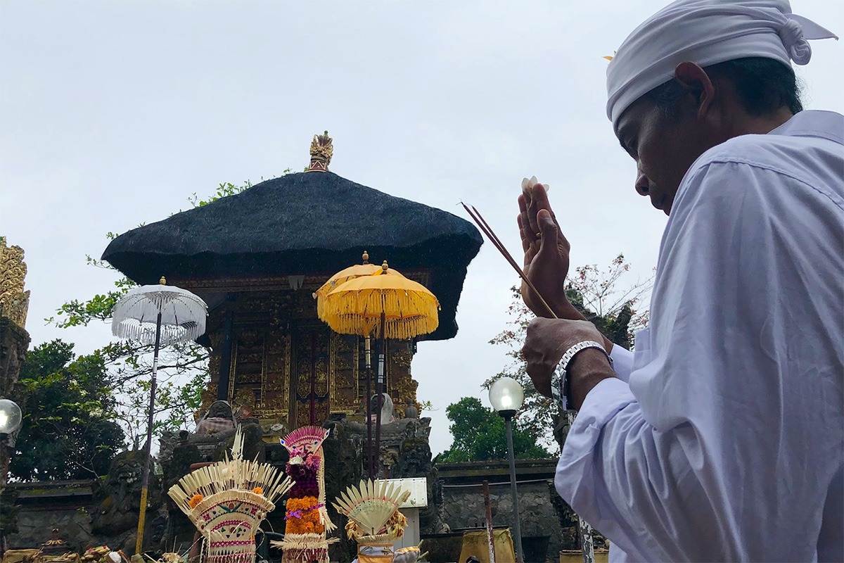 A Balinese mangku (spiritual leader) reciting prayers in a Balinese temple. Photo by Bill Witter