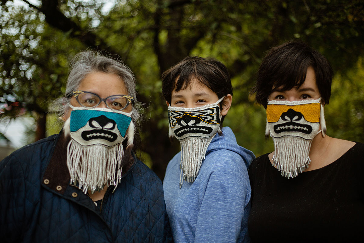 Three people, three generations of a family, pose outdoors wearing decorative beaded face masks.