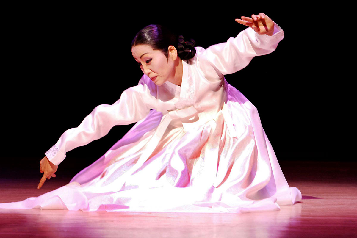 A woman in a long-sleeved pink gown crouches on a stage in a dance, with a spotlight on her.