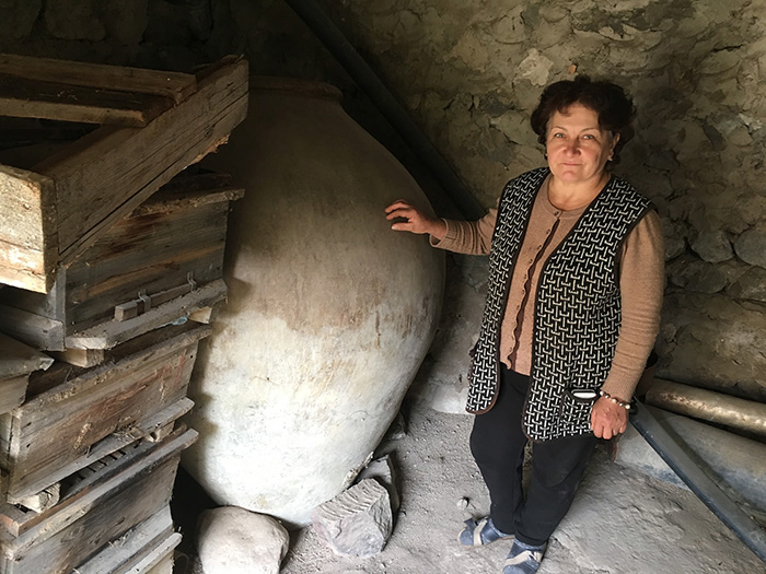 Asli Saghatelyan stands next to her father-in-law's 240-gallon karas, a clay vessel traditionally used in Armenia, until recently, for storing and fermenting homemade wine. Photo by Karine Vann, Smithsonian