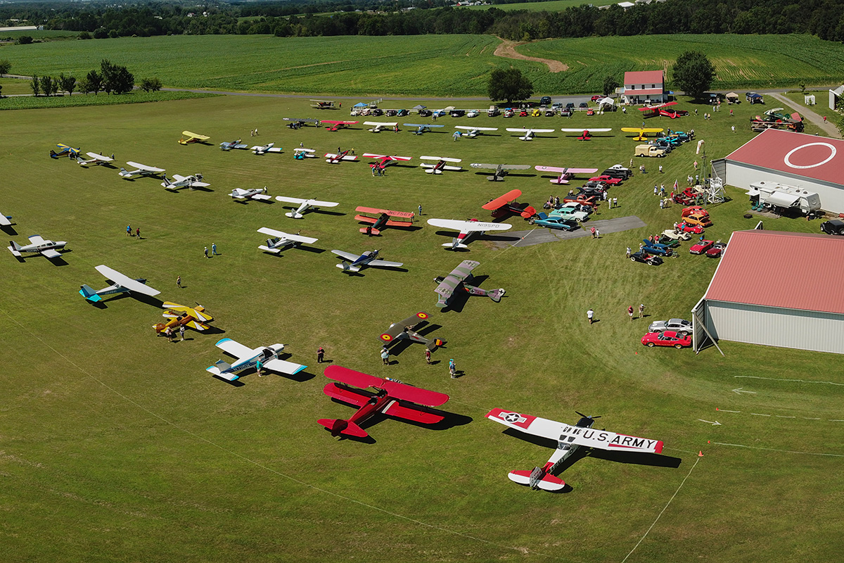 An aerial view of the Golden Age Air Museum main field covered in airplanes, both belonging to the museum and to visitors who flew in. Photo by Glenn Riegel, © Glenn Riegel Photography