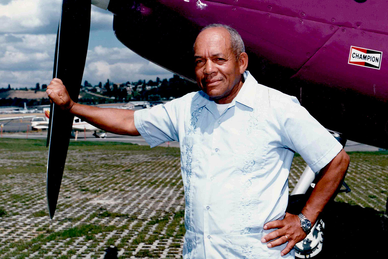 Airplanes accompanied James Wiley throughout his life. In 1990, he poses beside an airplane on display at a Seattle area air show. Photo courtesy of Bill Wiley