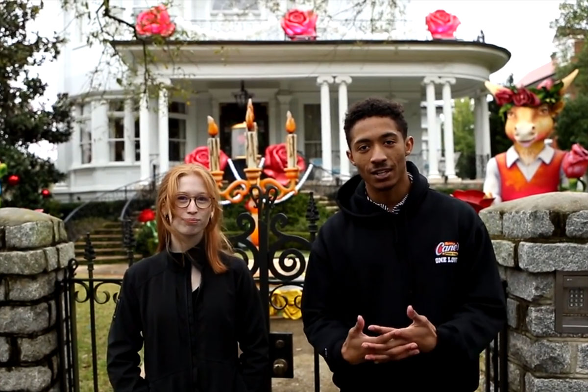 Two young people stand in front of a white house adorned with decorations.