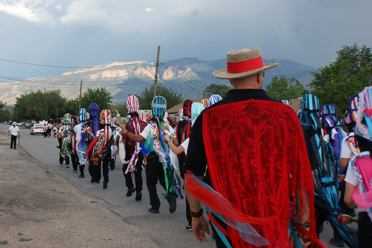 A procession along a rural road, with people in colored oval-shaped headdresses. Mountains in the distance.