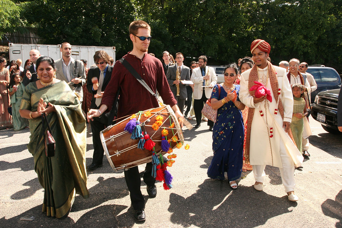 After composing and transcribing music for my wedding day, Red Baraat was born. Dave Sharma leads the baraat (wedding procession) on dhol, as I walk with my mother, family, and friends. August 27, 2005. Photo courtesy of Sunny Jain