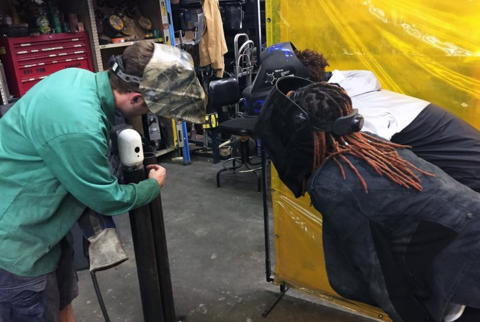 Students and staff examine the quality of welds at the Folklife Fabrication Shop. Photo by Kyle Bancroft