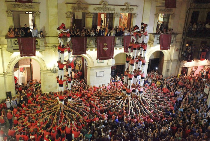 Human tower-building teams Colla Joves and Colla Vella from Valls, Tarragona, perform in front of the city hall. <em>Castells</em> were first documented as a Catalan cultural form in 1801. Photo by Pere Toda/Ajuntament de Valls