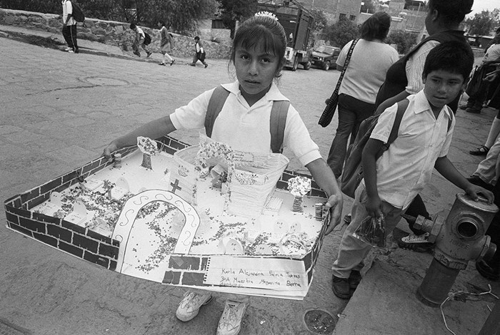 A young student of Valle de Allende, Mexico, is on her way to school. She carries her homework assignment, an altar for Día de los Angelitos, the first of three days when participants honor and commune with deceased ancestors. She has constructed the San Miguel Church graveyard, where she and her family will spend the third day, Día de los Muertos. Her name and the name of her teacher appear on the churchyard wall. Photo by Miguel Gandert