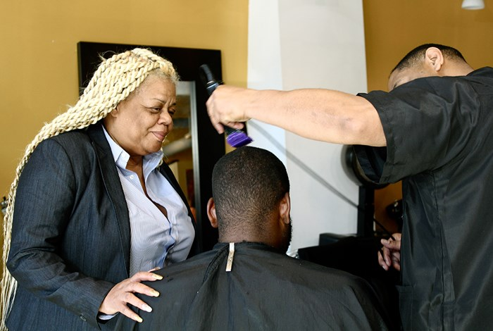 Wanda Henderson checks in on barber Martin Willis and his client at Wanda's on 7th. Photo by Angela Calonder
