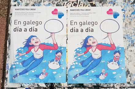 "Street posters encouraging people to join the Galician language parade on May 17, 2018, organized by Queremos Galego (""We Want Galician""). The main text reads, ""In Galician day by day."""