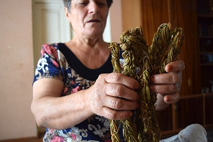 Greta Grigoryan reveals the aveluk she collected from fields nearby and braided in the spring. Photo by Karine Vann, Smithsonian