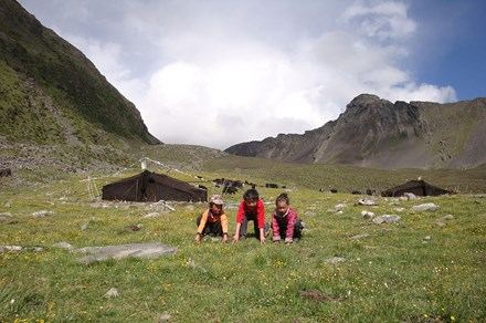 Two of my younger brothers with our neighbor's daughter play in front of the black yak-hair tents.