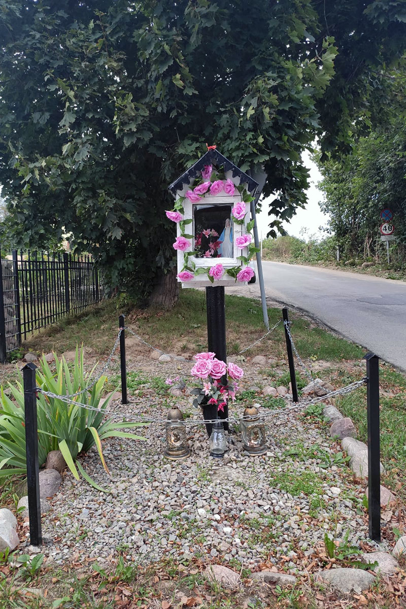 A roadside shrine adorned with pink roses.
