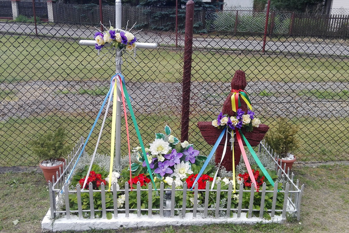 A small roadside shrine decorated with colored ribbons and white, red, and purple flowers.