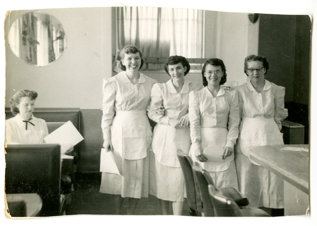 Four women in a diner, wearing matching waitress uniforms and aprons, all smiling. Black-and-white photo.