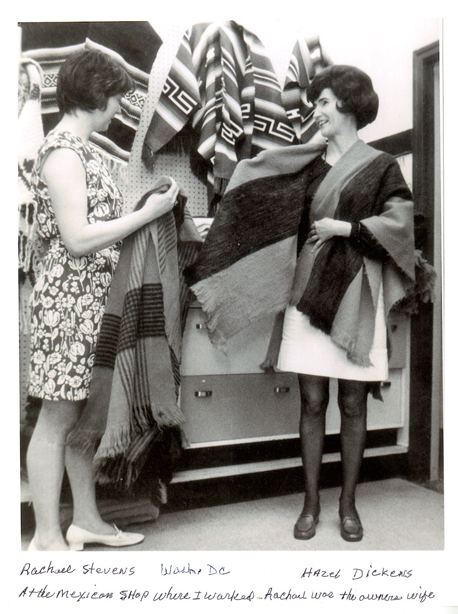 "Two women in a store, holding and wearing woven shawls. Handwritten text below the photo labels Rachael Stevens on the left, Hazel Dickens on the left. It reads, ""Wash. DC / At the Mexican shop where I worked - Rachael was the owners wife."""