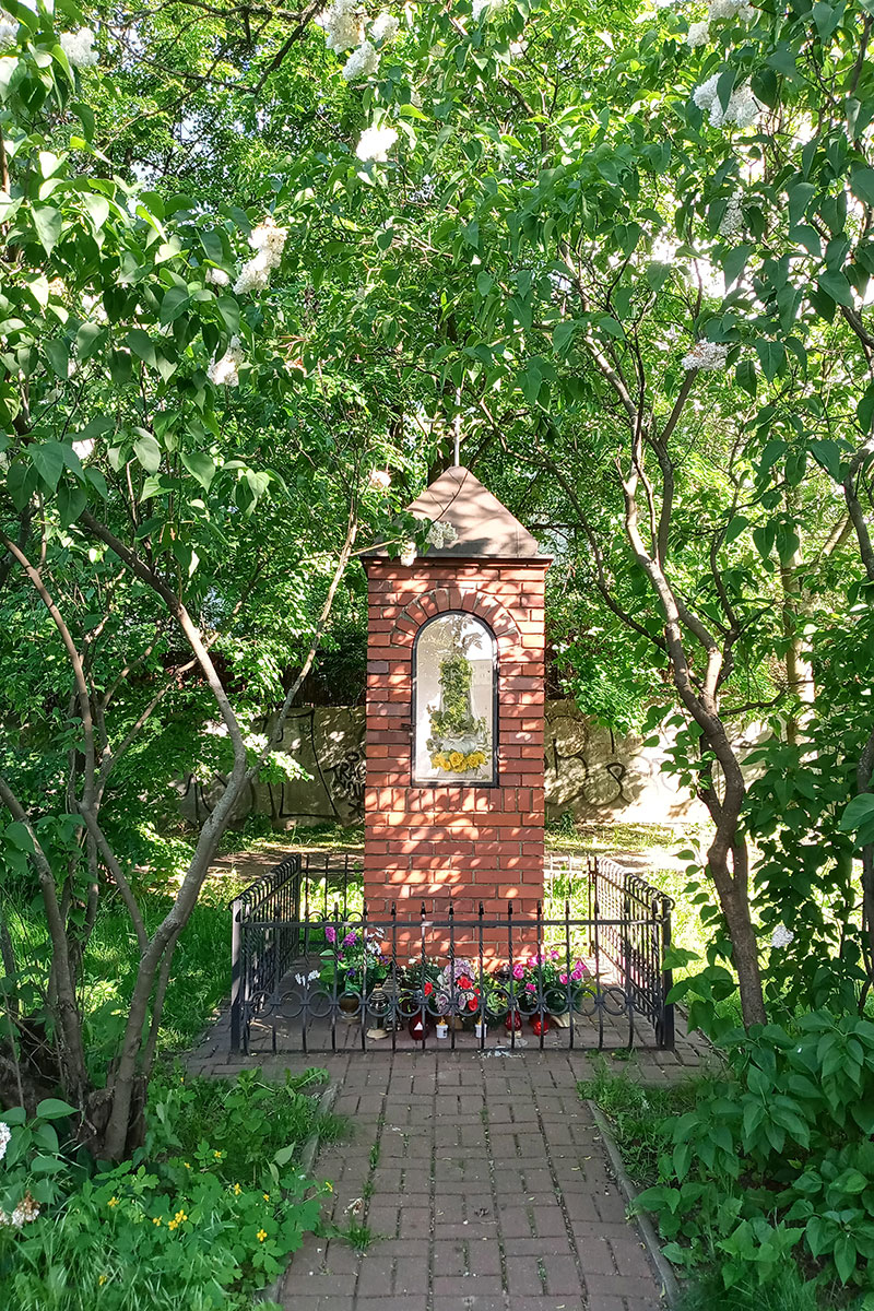 A red brick shrine amid lush greenery, with a brick walkway leading to it.