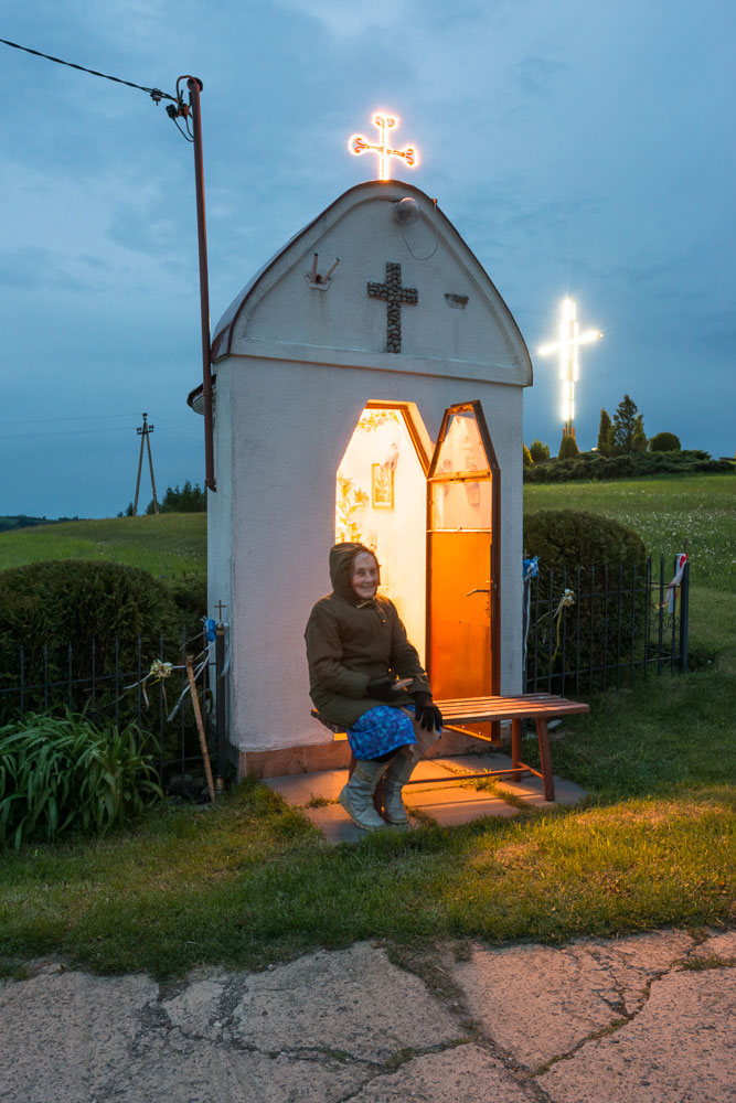 At dusk, someone sits outside a roadside shrine warmly lit from within. Two crosses on the outside glow against the dark sky.