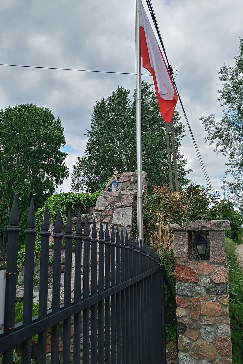 A stone shrine along a wrought-iron fence, with a flagpole alongside.