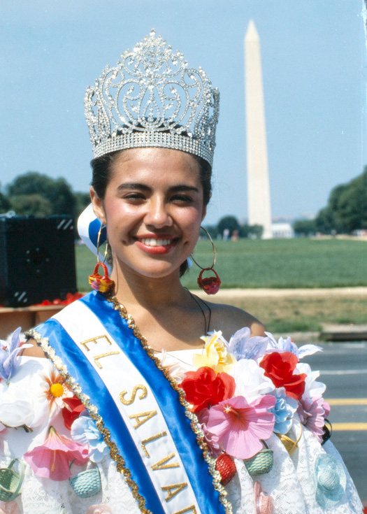 A woman poses smiling with the Washington Monument in the background. She wears a crown, a sash with the words El Salvador, and a white blouse with colorful floral detail