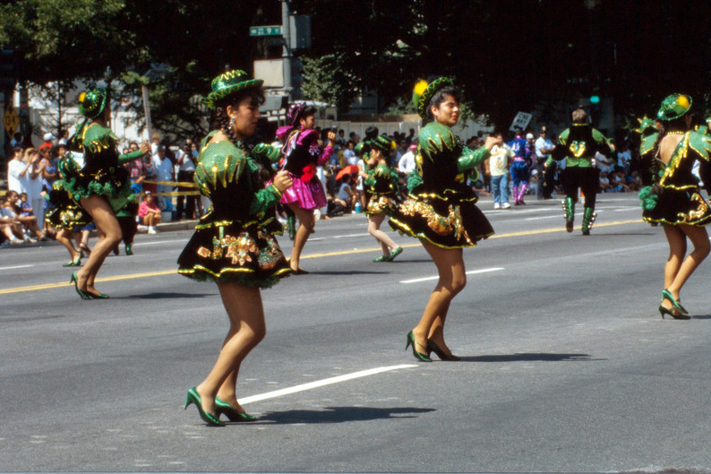 Dancers parade down the street in short green dresses, green hats, and green shoes