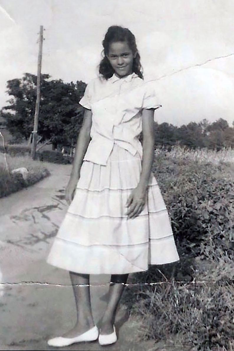 A teenage girl poses for a photo on a rural road. The black-and-white photo has been crinkled and stained.