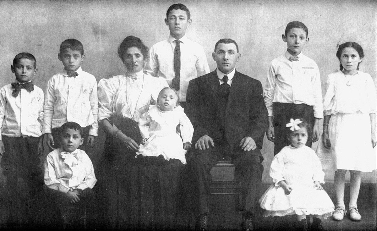 Old black-and-white photo two parents and eight children, the youngest a baby in the mother's lap.