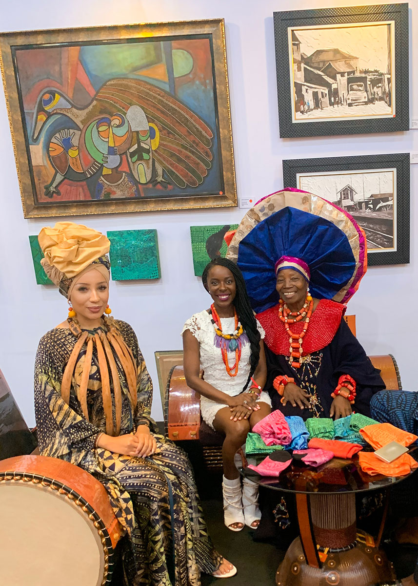 Three women sit and pose, surrounded by art and textiles.