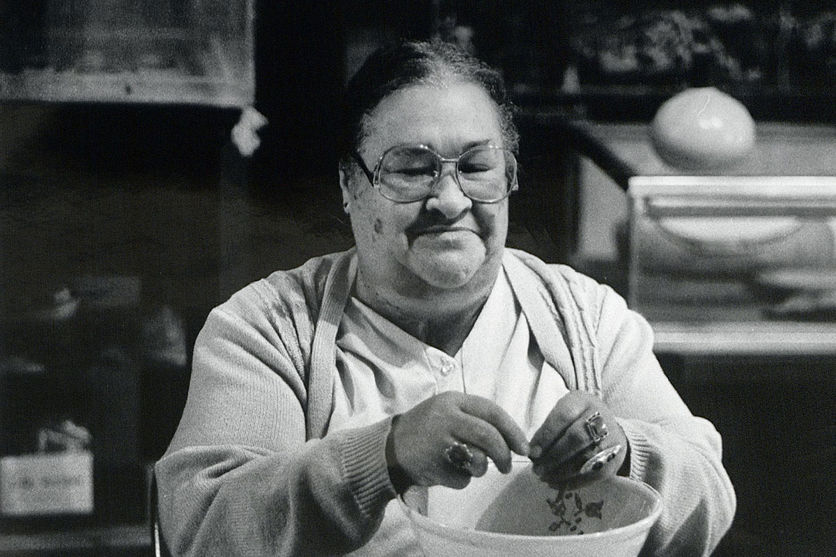A woman in large glases sits at a kitchen table, working over a porcelain bowl.