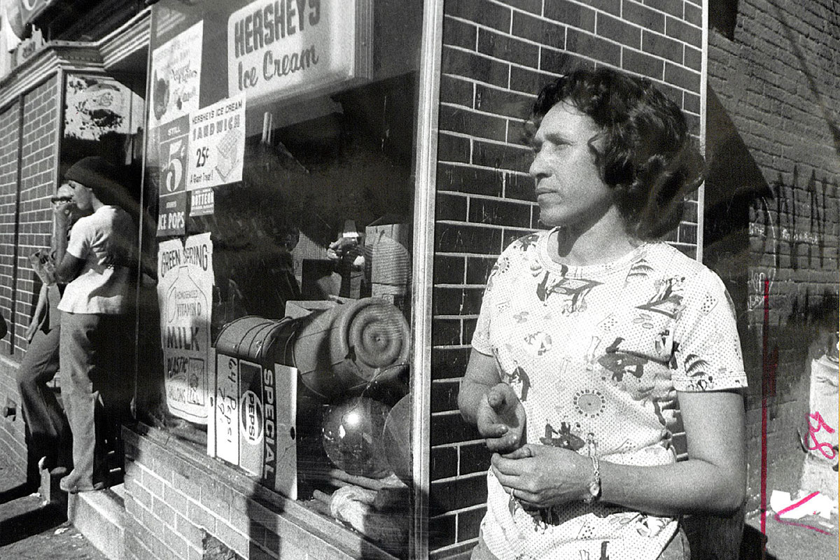 A woman stands outside a corner convenience store. Black-and-white photograph.