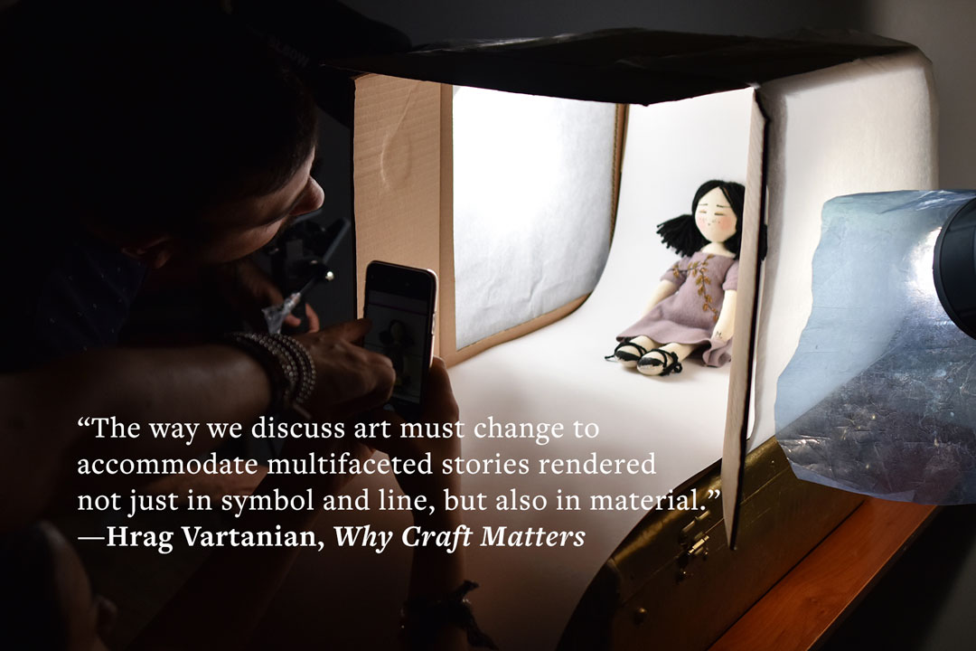 "A man is bent over to look into a handmade light box containing a small, handmade cloth doll. In front of the light box, a person holds a phone to capture a photo of the doll. A quote is overlaid: ""The way we discuss art must change to accommodate multifaceted stories rendered not just in symbol and line, but also in material."" –Hrag Vartanian, Why Craft Matters."