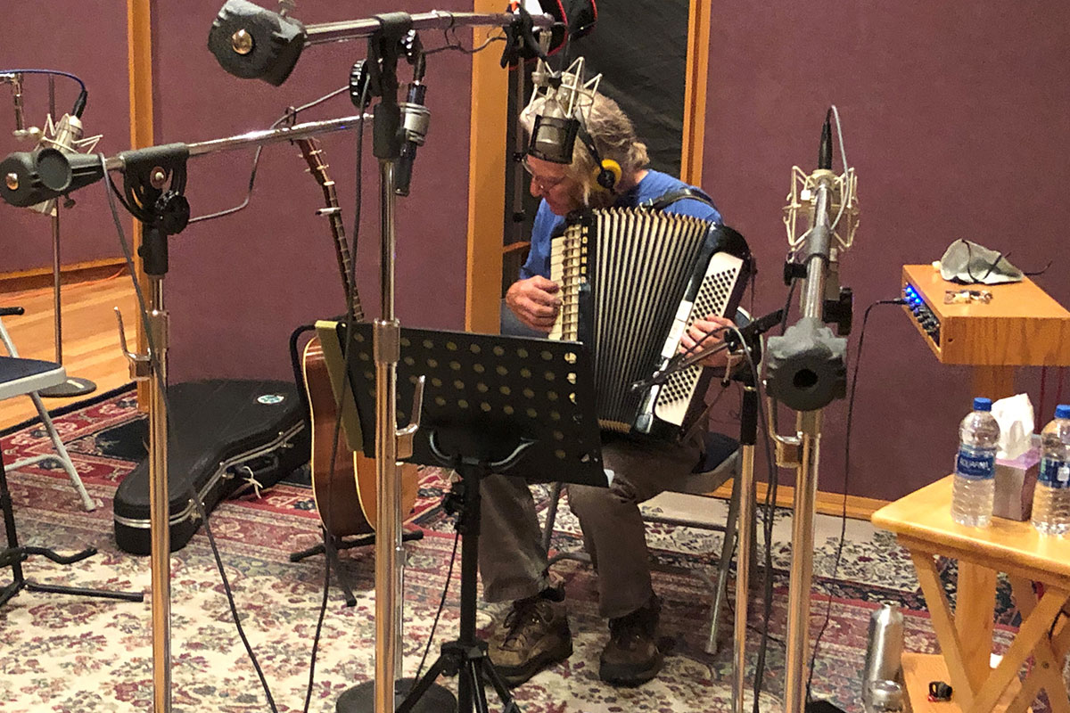 A man plays accordion in a home recording studio, surrounded by mic stands. With headphones on, he tilts one ear to his instrument.