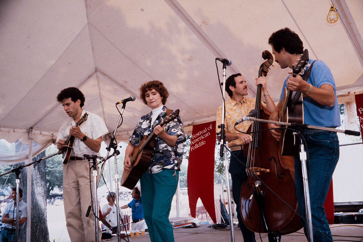 Four people on stage, three men and a woman, with a banner behind them for the Festival of American Folklife. The woman plays guitar; the men play mandolin, upright bass, and guitar.