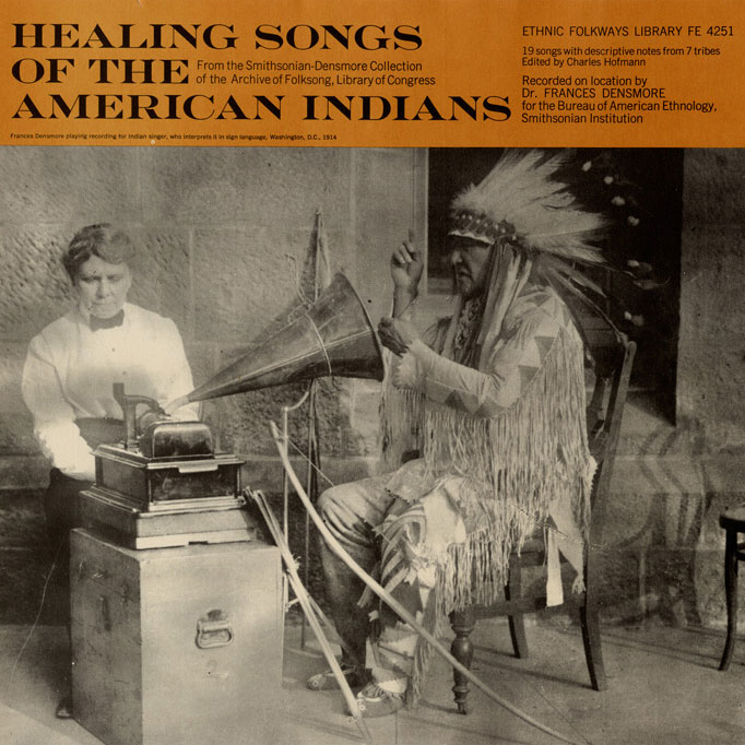 "Cover art for the album ""Healing Songs of the American Indians"" with a black-and-white photograph of a Native American man in full regalia sitting in front of a phonograph."