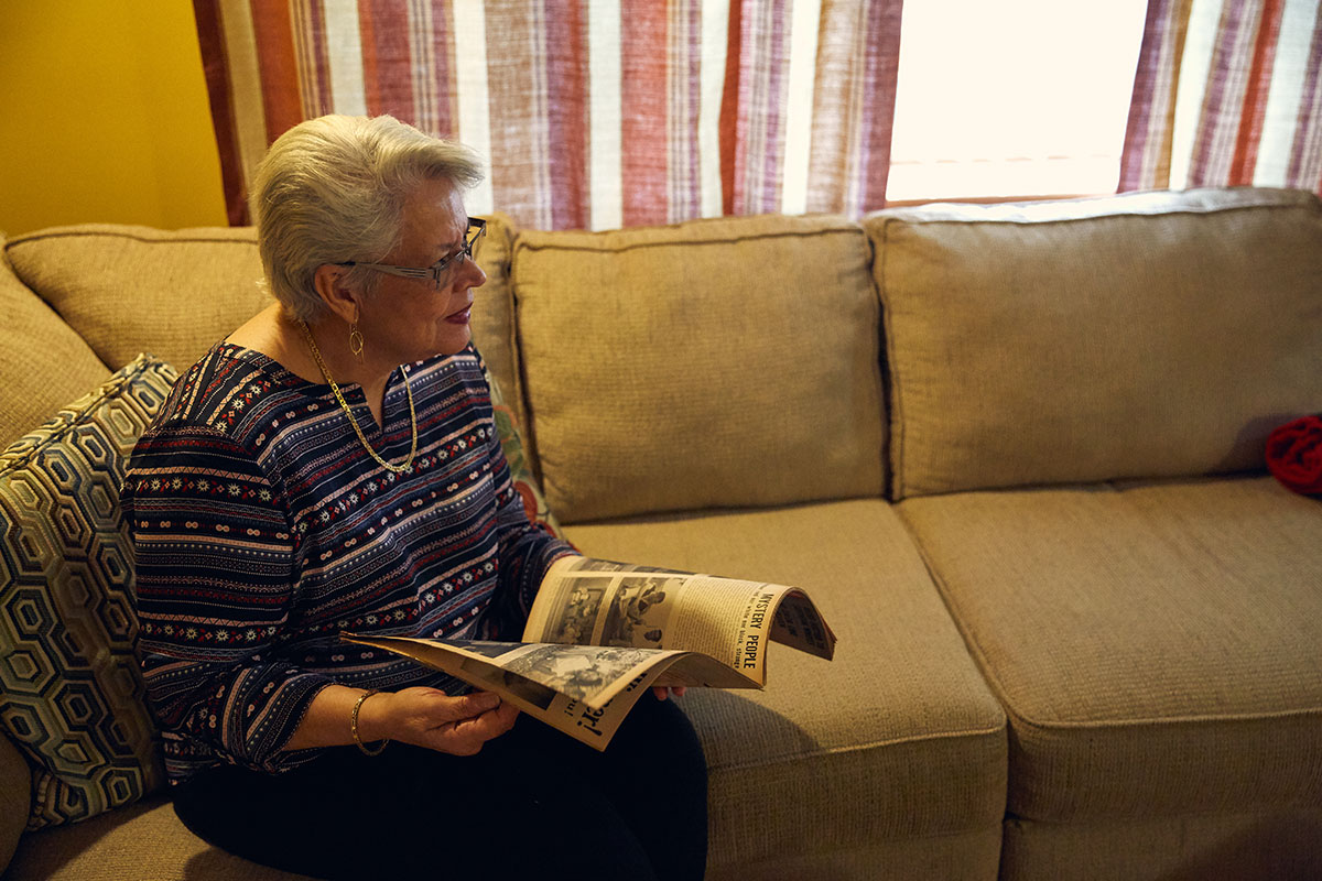 A woman on a couch at home holds open the magazine containing the previous spread, looking a bit dismayed to find a photo of herself.
