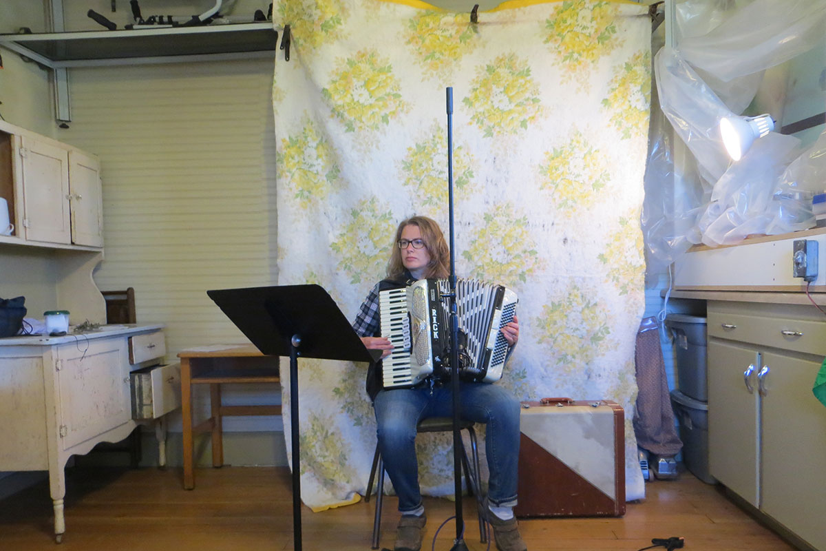 A woman with long dirty blonde hair, plaid shirt, and jeans plays a pearly white accordion, reading from a music stand. Behind her, she has rigged up a floral quilt to dampen the sound. To  her sides are cabinetry and a small lamp pointed at her.