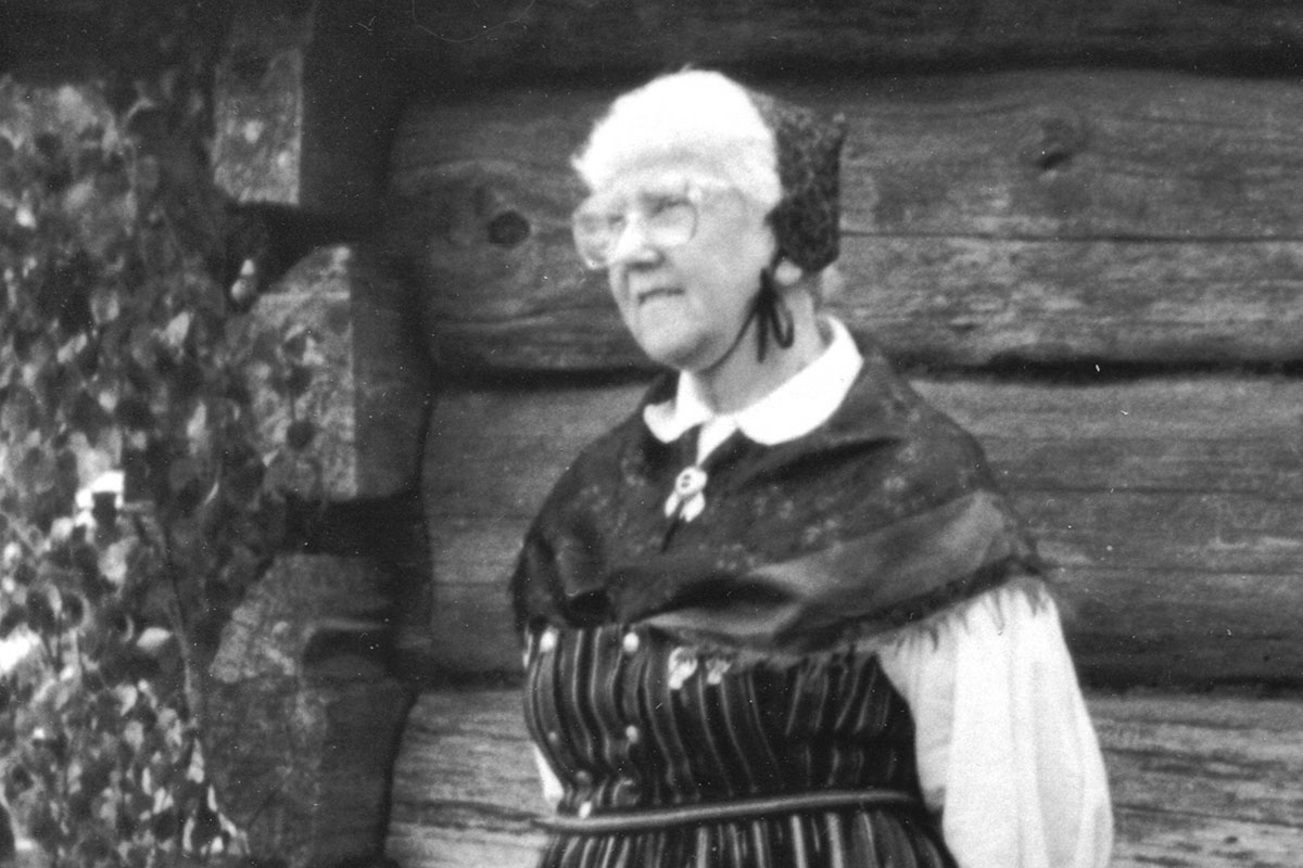 An elderly woman with white hair and blouse and dark bonnet, shawl, and dress. Black-and-white photograph.