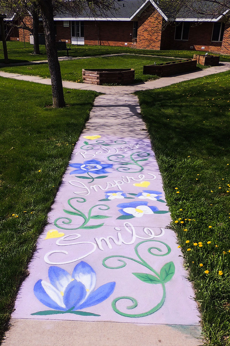 A chalk mural on a sidewalk leading toward a red brick building with the words SMILE, INSPIRE, and BELIEVE surrounded by blue and yellow flowers and green leaves and stems.