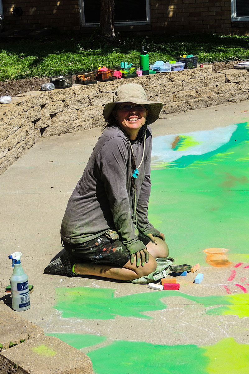 In the same scene as the previous picture, the woman kneeling looks up and smiles at the camera, her face half hidden by a wide-brimmed hat. Her legs, hands, and clothes are covered in chalk smudges.