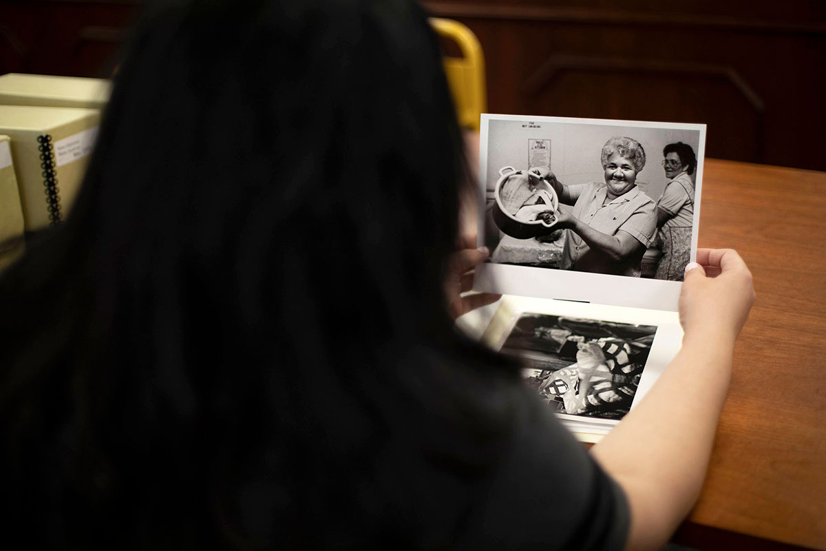A woman holds up a photo in a manilla folder, portraying an older woman working in a kitchen.
