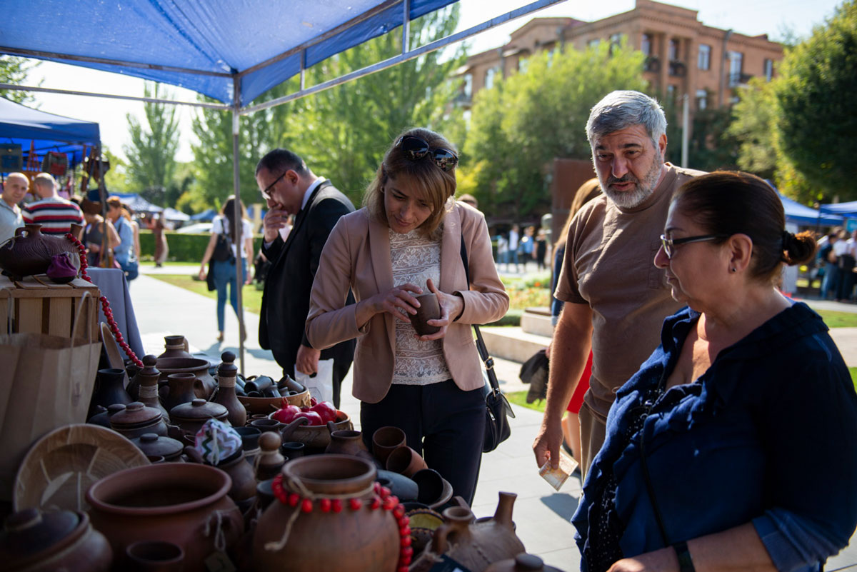 At an outdoor market, four people stand to the right of a table full of handmade pottery. A woman in the center of the image holds a small clay cup in her hands.