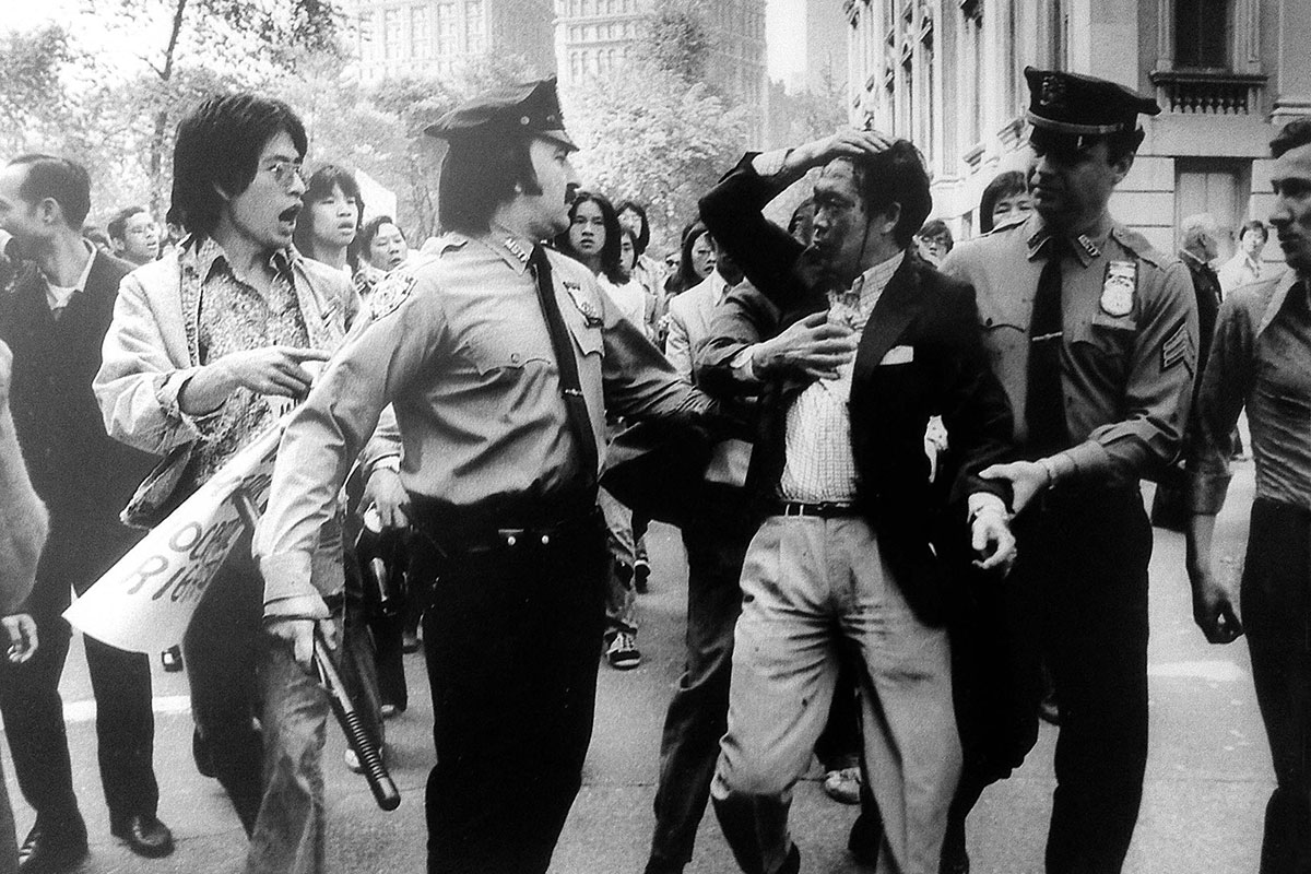 In the foreground, three police officers confront and hold back an Asian man who is holding his hair back, his face covered in blood. Behind them is a group of Asian men and women, one yelling at the police. Black-and-white photo.