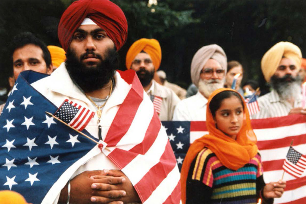 In the foreground, a man in a dastār (turban) wrapped in an American flag looks sternly at the camera. Behind him are other men and one young woman in dastārs hold small and large American flags.