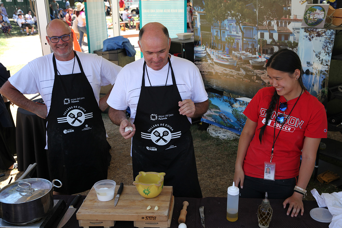 On the left, two twin brothers in white shirts and black aprons preside over an outdoor kitchen counter with a dish in the making. On the right, Josi (the author) in a red Denison Soccer T-shirt looks at the items on the counter, laughing. In the background, people mill around on the National Mall.