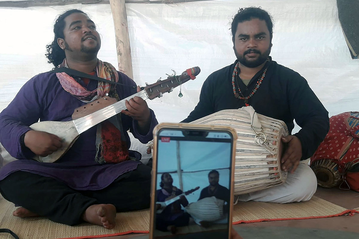 Two brothers play music on a long-necked string instrument and a barrel-shaped drum. An iPhone is in the foreground, filming them.