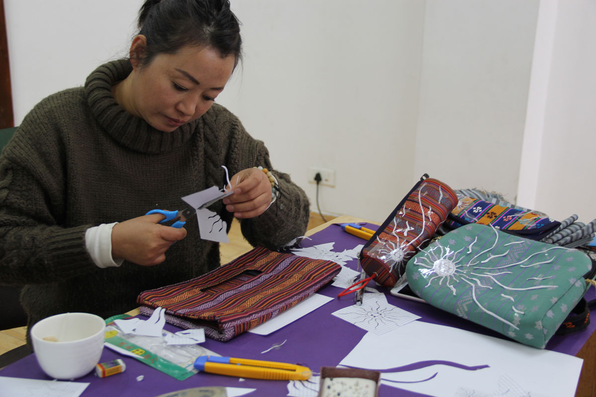 A woman sits at a table covered with prototypes of her bag designs. She holds a pair of scissors and cuts a piece of paper into the shape of a sun for an embroidery pattern.